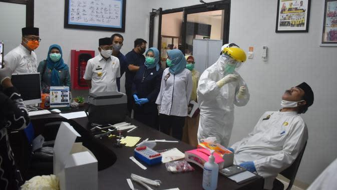 Tenaga Medik Balai POM Mamuju saat melakukan pengambilan spesimen swab pasien (Liputan6.com/Abdul Rajab Umar)