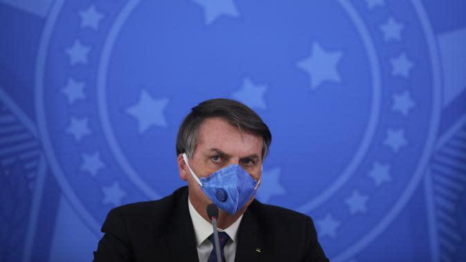 Presiden Brasil Jair Bolsonaro mengenakan masker saat konferensi pers mengenai pandemi virus corona COVID-19 di Istana Planalto, Brasilia, Brasil, 20 Maret 2020. (Sergio LIMA/AFP)