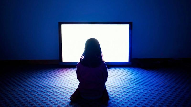 Image of child watching TV in the dark, 16:9 scaled