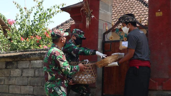 Komandan Kodim 1626/Bangli Letkol HTL turun langsung membagikan makanan ke rumah-rumah warga yang diisolasi (Liputan6.com/Dewi Divianta)