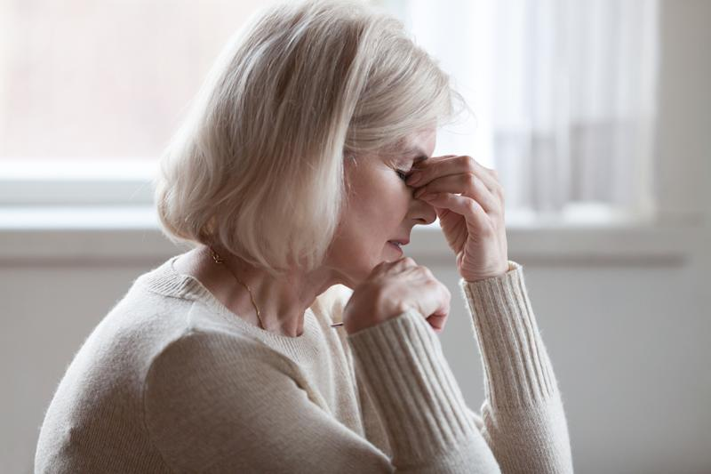 Fatigued upset middle aged older woman massaging nose bridge feeling eye strain or headache trying to relieve pain, sad senior mature lady exhausted depressed weary dizzy tired thinking of problems