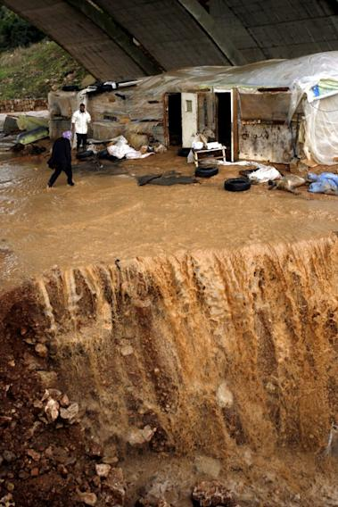 A woman crosses despite of the water that overflows after heavy rains and big wind on January 7, 2013 in the Lebanese southern city of Jadra. Stormy weather, including high winds and heavy rainfall, lashed Israel and the Palestinian territories on Monday, downing powerlines and trees and causing several injuries.  AFP PHOTO MAHMOUD ZAYYAT
