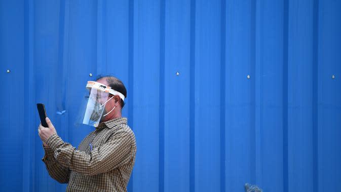 Seorang pria menggunakan ponselnya di sepanjang pinggir jalan di New Delhi (16/9/2020). Total kasus Covid-19 di India melampaui lima juta pada 16 September, data kementerian kesehatan menunjukkan Pandemi meluas cengkeramannya di negara tersebut. (AFP/Sajjad Hussan)