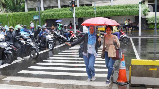 Pejalan kaki melintas menggunakan payung saat hujan mengguyur kawasan Jakarta, Senin (3/2/2020). Badan Meteorologi, Klimatologi, dan Geofisika (BMKG) merilis informasi peringatan dini cuaca ekstrem yang diperkirakan berlangsung hingga Rabu (5/2/2020) mendatang. (Liputan6.com/Angga Yuniar)