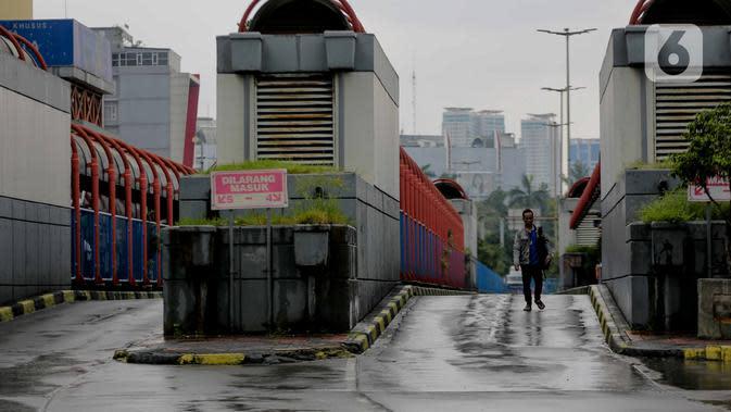 Calon penumpang melintas di jalur bus di kawasan Terminal Blok M, Jakarta, Selasa (24/3/2020). Pemprov DKI Jakarta membatasi aktivitas warga diluar rumah untuk mencegah penyebaran Covid-19 di ruang publik. (Liputan6.com/Faizal Fanani)