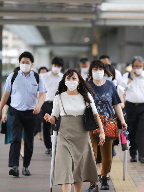 Orang-orang yang mengenakan masker berjalan di Minato-ku, Tokyo, Jepang (30/6/2020). Pemerintah kota metropolitan Tokyo mengonfirmasi kasus infeksi baru COVID-19 yang telah mencapai angka 50 di tengah kekhawatiran kemunculan kembali kasus penularan. (Xinhua/Du Xiaoyi)
