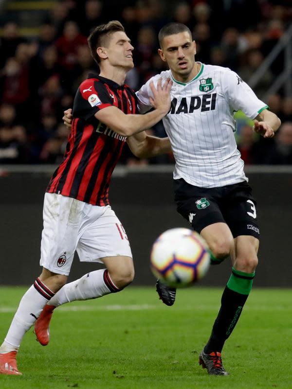 Striker AC Milan, Krzysztof Piatek berebut bola dengan bek Sassuolo, Merih Demiral selama pertandingan lanjutan Liga Italia di stadion San Siro (2/3). Kemenangan ini mengantar Milan masuk tiga besar klasemen melangkahi Inter Milan. (AP Photo/Luca Bruno)