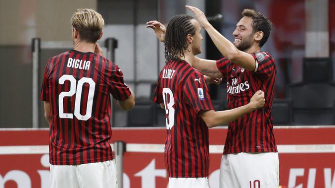 Pemain AC Milan Hakan Calhanoglu (kanan) merayakan golnya ke gawang Atalanta pada pertandingan Serie A di Stadion San Siro, Milan, Italia, Jumat (24/7/2020). Pertandingan berakhir 1-1. (AP Photo/Antonio Calanni)