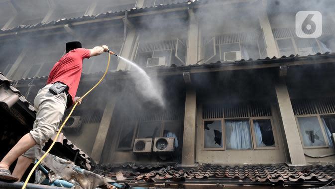Seorang pria berusaha memadamkan api saat kebakaran kembali terjadi di Gedung SMK Yadika 6, Jatiwaringin, Pondok Gede, Bekasi, Jawa Barat, Selasa (19/11/2019). Guru, siswa, dan pegawai berjibaku memadamkan api sambil menunggu petugas pemadam kebakaran datang. (merdeka.com/Iqbal Nugroho)