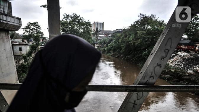 Warga melintasi jembatan di atas Kali Ciliwung di Rawajati, Jakarta, Selasa (22/9/2020). Banjir kiriman bukanlah hal baru bagi warga RW 07 Rawajati, namun dampaknya selama bertahun-tahun sangat terasa dengan munculnya deretan rumah rusak hingga ditinggalkan pemilik. (merdeka.com/Iqbal S. Nugroho)