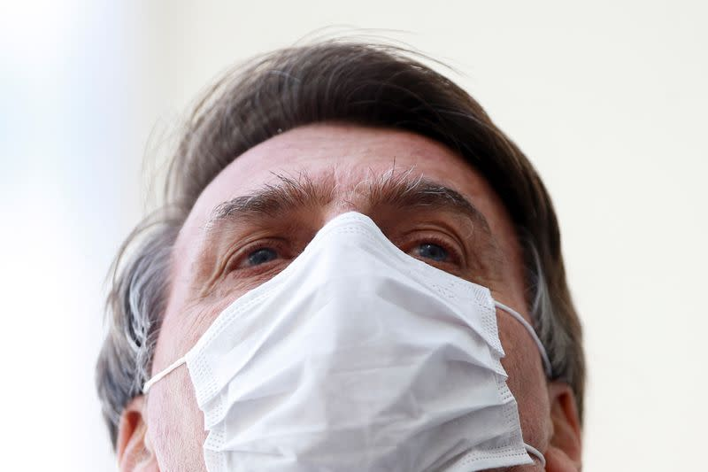 Brazil's President Jair Bolsonaro wearing a protective mask speaks with journalists, amid the coronavirus disease (COVID-19) outbreak, at the Planalto Palace, in Brasilia