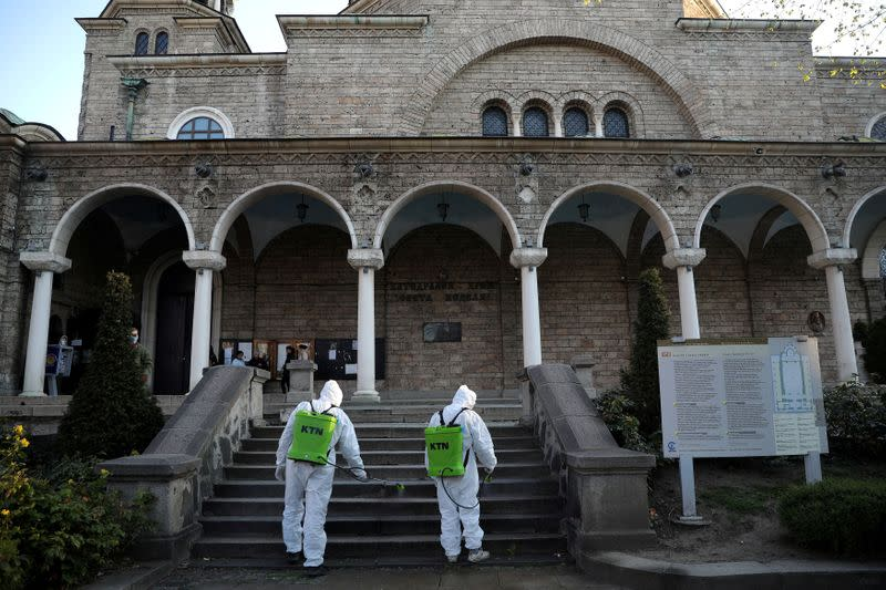 FILE PHOTO: Workers spray disinfectant outside St Nedelya church