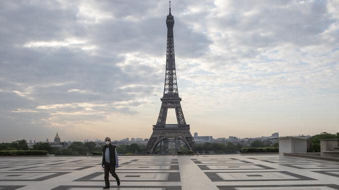 Seorang pria memakai masker saat berjalan di Alun-Alun Trocadero, Paris, Prancis, Jumat (24/4/2020). Prancis menempati posisi keempat sebagai negara dengan kasus infeksi virus corona COVID-19 terbesar di dunia yaitu 165.962 positif dengan 46.293 orang sembuh. (AP Photo/Michel Euler, FILE)
