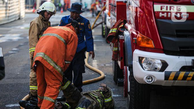 Petugas pemadam kebakaran membantu rekannya setelah melakukan pendingan di Kejaksaan Agung RI yang terbakar, Minggu (23/8/2020). Kebakaran di gedung Kejaksaan Agung pada Sabtu (22/8) malam akhirnya padam dan kini bangunan tersebut menyisakan bagian hitam legam. (Liputan6.com/Faizal Fanani)