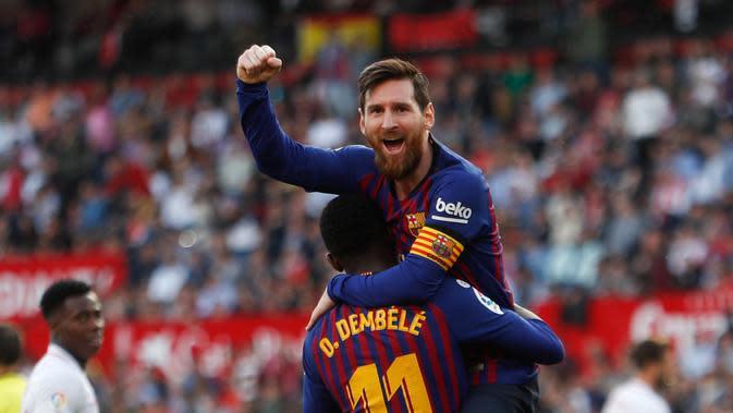 Penyerang Barcelona Lionel Messi memeluk rekan setimnya Ousmane Dembele usai mencetak gol ke gawang Sevilla pada laga La Liga di Stadion Ramon Sanchez Pizjuan, Sevilla, Sabtu (23/2). Barcelona menang 4-2. (AP Photo/Miguel Morenatti)