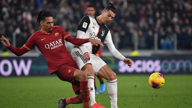 Pemain Juventus Cristiano Ronaldo (kanan) dan pemain AS Roma Chris Smalling berebut bola pada pertandingan Coppa Italia di Turin, Italia, Rabu (22/1/2020). Juventus menggilas AS Roma 3-1 dan berhasil lolos ke semifinal. (Marco Bertorello/AFP)