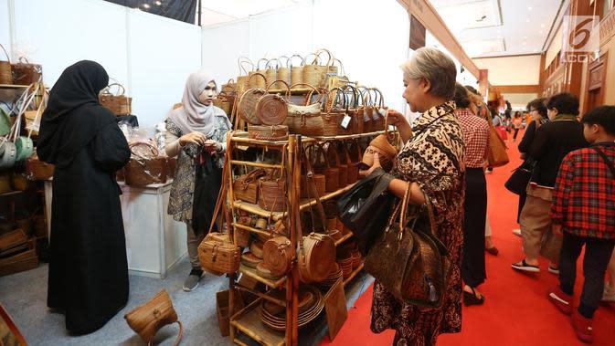Seorang wanita memilih tas dari rotan selama pameran inacraft 2019 di JCC, Jakarta, Rabu (24/4). Inacraft 2019 sendiri merupakan salah satu pameran produk kerajinan terbesar di Asia Tenggara yang diikuti sekitar 1.700 peserta dari seluruh Indonesia dan luar negeri. (Liputan6.com/Angga Yuniar)