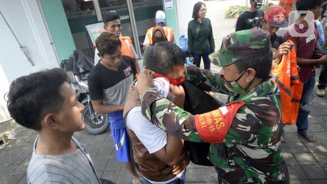 Tentara memakaikan masker kepada warga pelanggar PSBB yang terjaring Operasi Yustisi di BSD, Tangerang Selatan, Banten, Rabu (16/9/2020). Sanksi sosial lari sejauh 800 meter diberikan kepada warga pelanggar PSBB untuk memberikan efek jera. (merdeka.com/Dwi Narwoko)