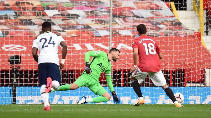 Gelandang Manchester United (MU) Bruno Fernandes mencetak gol penalti pada laga Liga Inggris melawan Tottenham Hostpur di Old Trafford, Minggu (4/10/2020). (AFP/Oli Scarff)