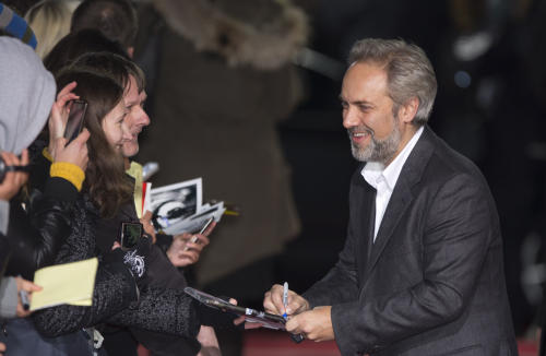 "FILE - A Tuesday, Oct. 30, 2012 photo from files showing British director Sam Mendes signing autographs as he arrives for the German premiere of the James Bond film ""Skyfall"" in Berlin. The return of director Sam Mendes and a long-awaited musical by Tori Amos are among productions slated for the 50th anniversary season at Britain's National Theatre, Wednesday, Jan. 30, 2013. ""Skyfall"" filmmaker Mendes will direct a production of Shakespeare's ""King Lear,"" starring Simon Russell Beale, opening next January. The 2013 season will see ""The Light Princess,"" a musical adaptation of a 19th-century fairytale by Amos and playwright Samuel Adamson. First announced two years ago, it will finally open in October. (AP Photo/Gero Breloer, File)"