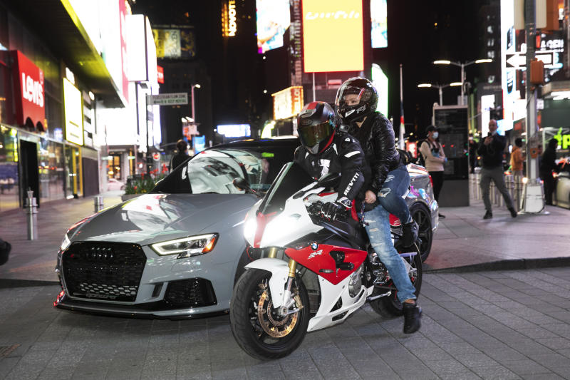 In this Saturday, May 2, 2020 photo, a sports car and motorcyclists are part of the scene in New York's Times Square during the coronavirus pandemic. Car mavens and motorcyclists normally wouldn't dare rev their engines in Midtown, but now they're eagerly driving into the city to take photos and show off for sparse crowds walking through the commercial hub. (AP Photo/Mark Lennihan)