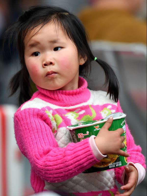 Seorang anak menunggu kereta api di Stasiun Kereta Selatan Guangzhou saat arus mudik Tahun Baru Imlek di Guangzhou, Provinsi Guangdong, China selatan (16/1/2020). Tahun Baru Imlek jatuh pada 25 Januari tahun ini. (Xinhua/Liu Dawei)
