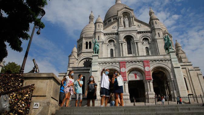 Wisatawan berjalan-jalan di basilika Sacre Coeur di distrik Montmartre, Paris pada Senin (10/8/2020). Penggunaan masker mulai hari Senin (10/8) diwajibkan di area luar ruangan yang ramai di ibu kota Prancis itu untuk mengendalikan peningkatan tingkat infeksi virus corona. (AP Photo/Michel Euler)