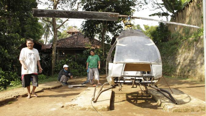 Gambar yang diambil pada 17 November 2019, Jujun Junaedi (kiri) menyelesaikan pembuatan helikopter buatannya di halaman belakang rumahnya di Sukabumi. Jujun yang berusia 41 tahun ini menargetkan helikopter berbahan bakar bensinnya rakitannya dapat diuji terbang pada akhir 2019. (Wulung WIDARBA/AFP)