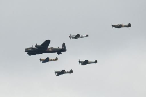 A World War II Lancaster bomber and Spitfire planes fly in formation to mark the centenary of the Royal Air Force, seen from the Wimbledon tennis championships