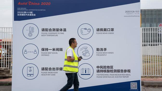 Pekerja melewati papan informasi mencegah penyebaran Covid-19 untuk peserta pameran Auto China 2020 di Beijing, Kamis (24/9/2020). Ajang Beijing International Automotive Exhibition 2020 (Auto China 2020) digelar mulai 26 September 2020 - 5 Oktober 2020 mendatang. (AP Photo/Ng Han Guan)