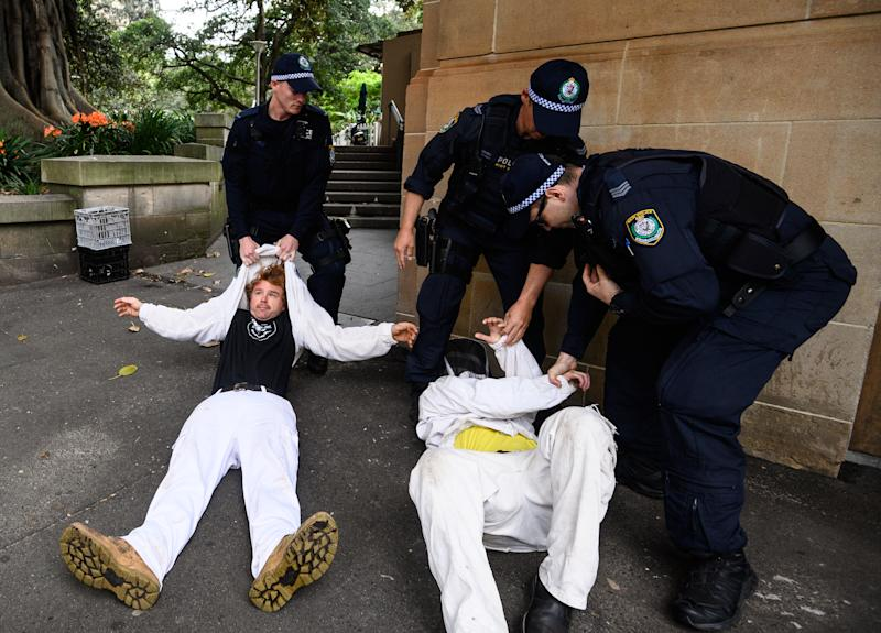 Police Officers drag activists from Extinction Rebellion out of the road in Elizabeth Street as they attempted to block traffic during a protest in Sydney onTuesday. Source: AAP/James Gourley