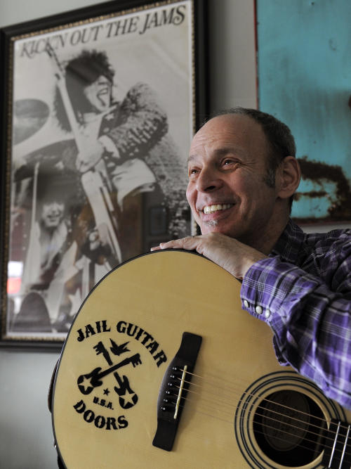 In this Jan. 16, 2012 photo, guitarist Wayne Kramer, founder of the band the MC5, poses with one of the instruments that will be provided to jail inmates as part of the Jail Guitar Doors USA initiative at his recording studio in Los Angeles. The Jail Guitar Doors program provides instruments to inmates who are using music as a means of achieving rehabilitation. (AP Photo/Chris Pizzello)