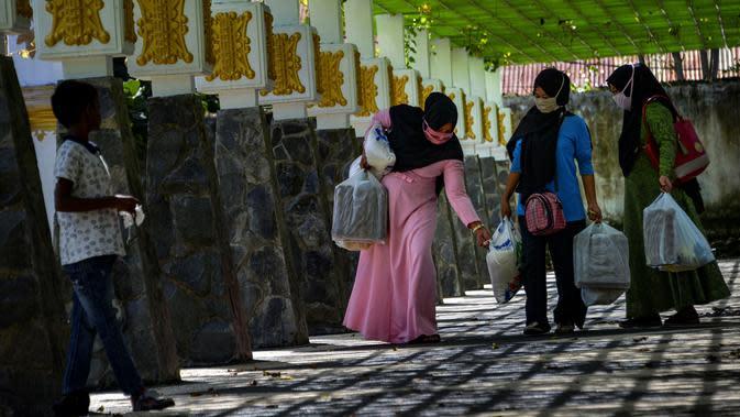 Warga usai membeli sembako murah di Banda Aceh, Aceh, Kamis (14/5/2020). Di tengah pandemi virus corona COVID-19, hadirnya penjualan sembako murah sangat membantu sebagian warga untuk memenuhi kebutuhan hidup. (CHAIDEER MAHYUDDIN/AFP)