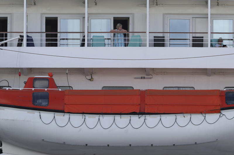 In this Friday, March 27, 2020, photo, passengers are seen on the cruise ship Artania docked at Fremantle harbour in Fremantle, Australia. Authorities were still hoping to fly 800 cruise ship passengers from Australia to Germany on the weekend, but a sharp overnight rise in cases of the new coronavirus on board brought severe complications for the repatriation mission. (Richard Wainwright/AAP Image via AP)