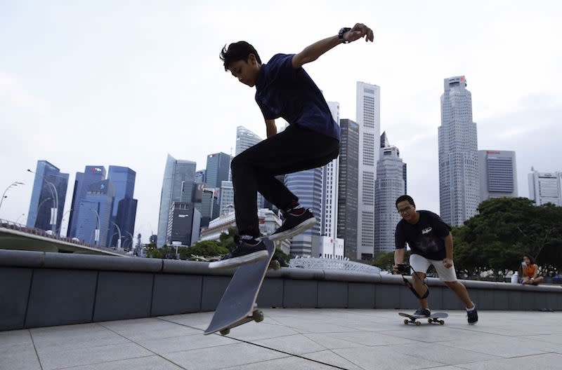 Youths skateboard in the evening at a park in the central business district in Singapore March 13, 2015. — Reuters pic
