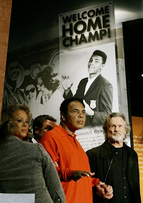 FILE - In this Nov. 18, 2005 file photo, boxing great Muhammad Ali is accompanied by his wife Lonnie and singer Kris Kristofferson as he tours the Muhammad Ali Center in Louisville, Ky. The man who became the world's most recognizable athlete was a baby sitter, a jokester and a dreamer in the predominantly black West End neighborhood of Louisville where he grew up and forged lasting friendships while beginning his ascent toward greatness. Now, as the iconic boxer slowed by Parkinson's disease prepares to turn 70 next week, he's coming home for a birthday bash at the downtown cultural center and museum that bears his name. (AP Photo/Ed Reinke, File)