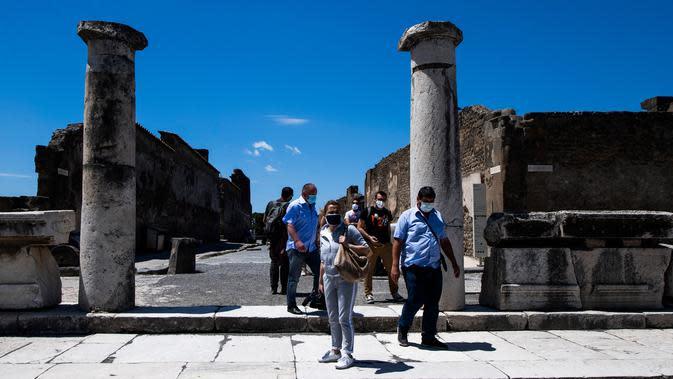 Orang-orang dengan mengenakan masker mengunjungi situs arkeologi Pompeii seusai kebijakan lockdown untuk mengendalikan penyebaran Covid-19 di Italia, Selasa (26/5/2020). Salah satu situs arkeologi paling terkenal di dunia ini dibuka kembali untuk umum pada 26 Mei. (Tiziana FABI / AFP)