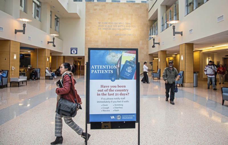 A sign about traveling greets incoming patients at the the U.S. Department of Veterans Affairs Pittsburgh Healthcare System University Drive campus, Tuesday, March 10, 2019, in Pittsburgh. The Pittsburgh VA said by the end of the week it will begin screening every person, whether a patient or not, who comes into its facilities for the novel coronavirus, using questions about symptoms and travel. (Andrew Rush/Pittsburgh Post-Gazette via AP)