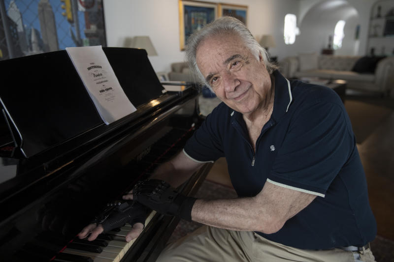 Brazilian pianist Joao Carlos Martins poses for pictures wearing bionic gloves, at his home in Sao Paulo, Brazil, Wednesday, Jan. 22, 2020. Martins, 79, was for decades Brazil's most acclaimed pianist, but an accident an a degenerative disease forced him to stop playing with both hands since 1998. That changed a few months ago when a new friend came to him with a pair bionic gloves that suit him perfectly. He can now play again with nine out of ten fingers. (AP Photo/Andre Penner)