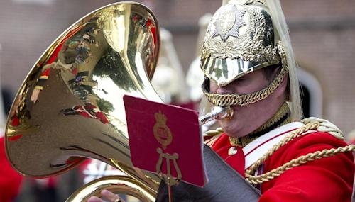 Tourists are reflected in the brass of a member of the Life Guards band as they escort a Colour party of the Grenadier Guards as they leave St James's Palace to change the guard at Buckingham Palace in London, Wednesday, Oct. 23,2013. Prince William and his wife Kate have asked seven people to be godparents to their son, Prince George, who will be christened at a major royal family gathering Wednesday, palace officials said. (AP Photo/Alastair Grant)