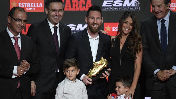Pemain Barcelona, Lionel Messi (tengah) berpose bersama istrinya Antonella Roccuzzo dan putra-putranya Thiago dan Mateo setelah menerima trofi Sepatu Emas keenamnya selama acara penyerahan di Antiga Fabrica Estrella Damm, Barcelona, Spanyol (16/10/2019). (AFP Photo/Josep Lago)
