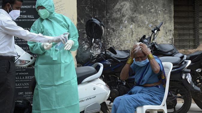 Seorang wanita bereaksi setelah memberikan sampel usapnya ke petugas kesehatan untuk menguji virus corona Covid-19 di daerah kumuh di Hyderabad (23/9/2020). Total 5,6 juta infeksi Covid-19 menempatkan India pada posisi kedua setelah AS. (AFP/Noah Seelam)