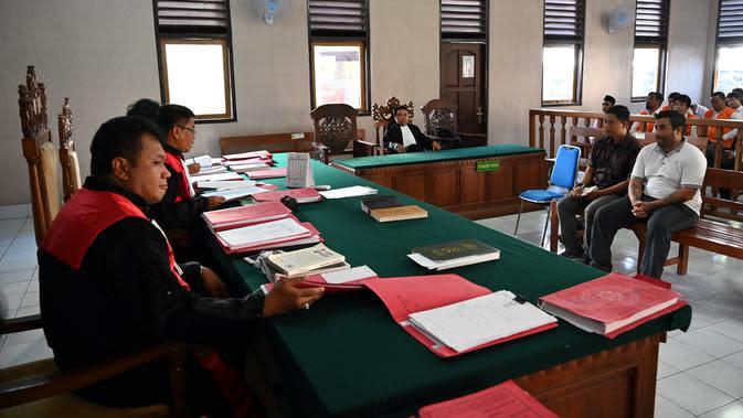 Warga Negara (WN) Amerika, Ian Andrew Hernandez (kanan) menjalani sidang pembacaan vonis di Pengadilan Negeri (PN) Denpasar, Bali, Senin (13/1/2020). Hakim memvonis Hernandez hukuman sembilan tahun dan empat bulan penjara karena berjualan narkoba sambil wisata di Bali. (SONNY TUMBELAKA/AFP)