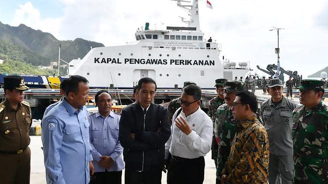 Presiden Joko Widodo (tengah) mendnegarkan penjelasan saat melakukan kunjungan kerja di Sentra Kelautan Perikanan Terpadu (SKPT), Natuna, Kepulauan Riau, Rabu (8/1/2020). Kunjungan Jokowi tersebut pascakapal coast guard milik China berlayar di perainan laut Natuna (HO/PRESIDENTIAL PALACE/AFP)