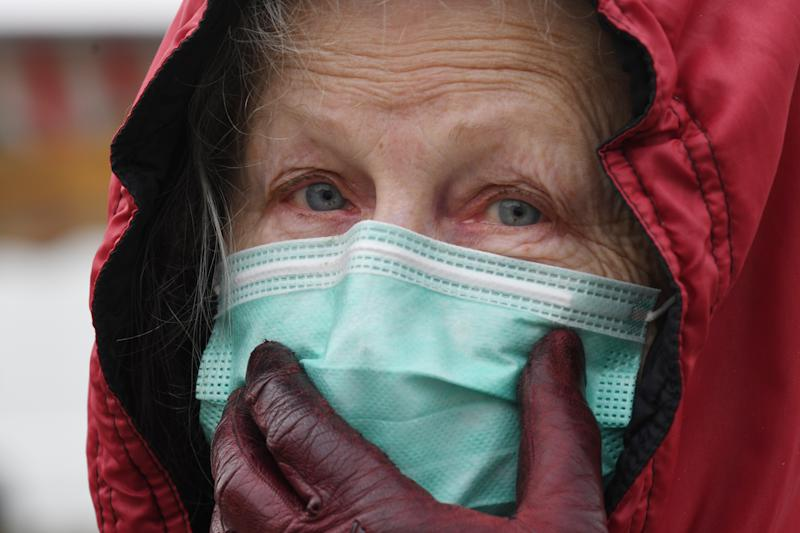 A woman wearing a protective face mask and gloves shops on a market, in Illiers-Combray, on April 3, 2020, amid the spread of the epidemic COVID-19 caused by the novel coronavirus. - France has been on lockdown since March 17 in a bid to limit the contagion caused by the novel coronavirus, a situation it has extended until a least April 15. (Photo by Jean-Francois MONIER / AFP) (Photo by JEAN-FRANCOIS MONIER/AFP via Getty Images)