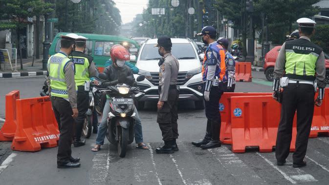 Sejumlah aparat kepolisian memeriksa pengendara yang melintas di Jalan Asia Afrika, Kota Bandung, saat diberlakukannya Pembatasa Sosial Berskala Besar (PSBB), Rabu (22/4/2020). (Liputan6.com/Huyogo Simbolon)