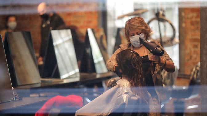 Seorang penata rambut melayani pelanggan di sebuah salon yang kembali dibuka di Brussel, Belgia, (18/5/2020). Belgia pada Senin (18/5) memasuki pelonggaran pembatasan tahap kedua dengan sekolah-sekolah membuka kembali beberapa kelas di bawah persyaratan organisasi yang ketat. (Xinhua/Zhang Cheng)