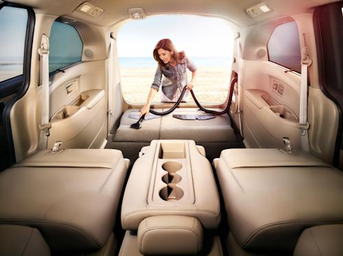 This publicity photo provided by American Honda Motor Co., Inc. shows an interior view of a 2014 Honda Odyssey Touring Elite, with an unidentified woman using a H-vac vacuum, in a beige leather interior. The world's first in-vehicle vacuum cleaner makes its debut on the updated 2014 Odyssey minivan. It's only available on the Touring Elite model, which starts at $44,450. (AP Photo/American Honda Motor Co., Inc.)