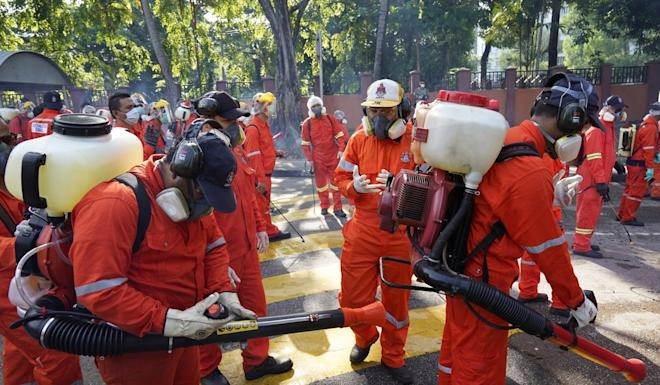 City health officials prepare to spray disinfectant on a street as a precaution against coronavirus in Kuala Lumpur on Saturday. Photo: AP