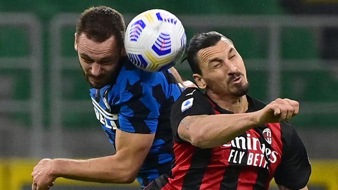 Penyerang AC Milan, Zlatan Ibrahimovic, berebut bola atas dengan bek Inter Milan, Stefan de Vrij, pada laga lanjutan Liga Italia di Stadion San Siro, Sabtu (17/10/2020) malam WIB. AC Milan menang 2-1 atas Inter Milan. (AFP/Miguel Medina)